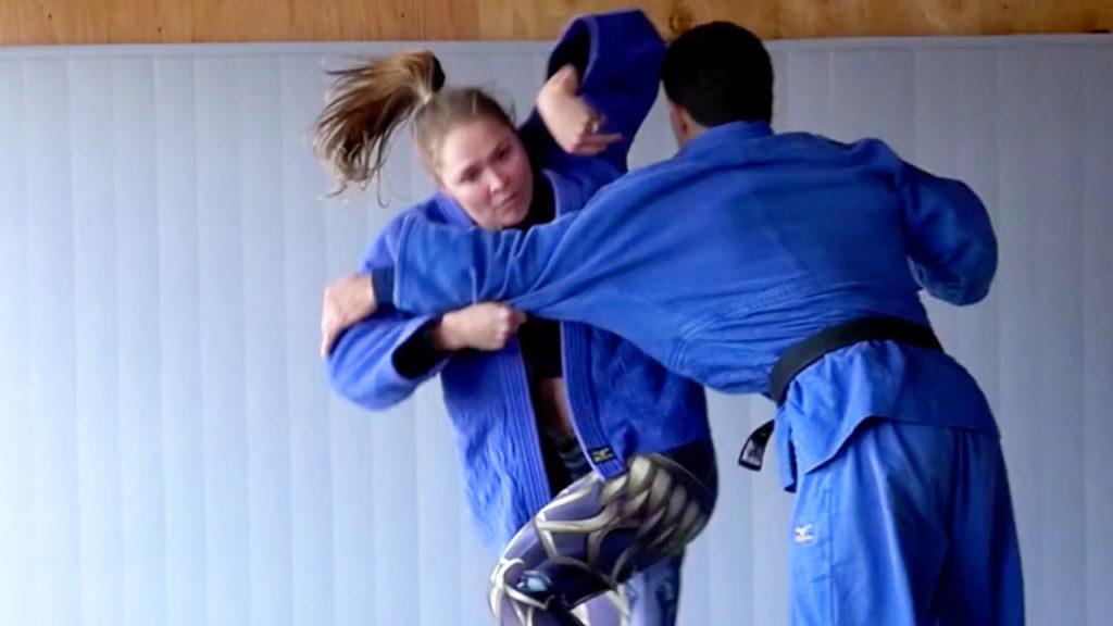 Ronda Rousey executing a judo throw on Justin Flores.