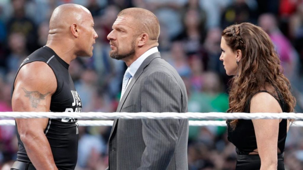 The Rock, Triple H, Stephanie McMahon (source: WWE)